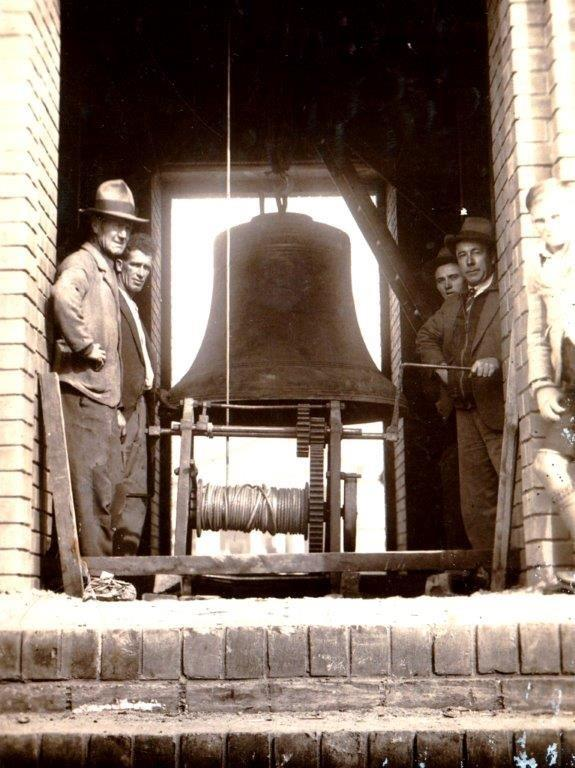 Installation of the largest bell in the Bathurst War Memorial Carillon, Builder Jim Newton holding the handle - June 1933